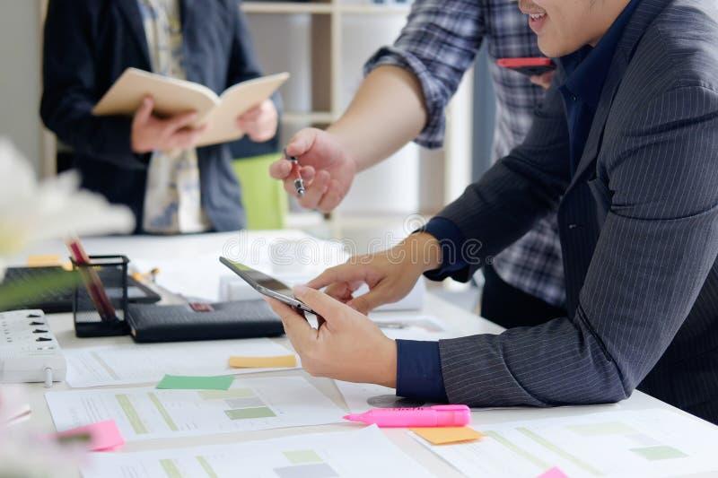 zaken die een drie bedrijfsmens raadplegen over bureau met vergadering stock afbeeldingen