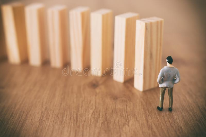 Zaken Een mens bevindt zich voor domino's en schikt hen maar is onbewust van het gevaar van hun daling risicocontrole en stock foto's