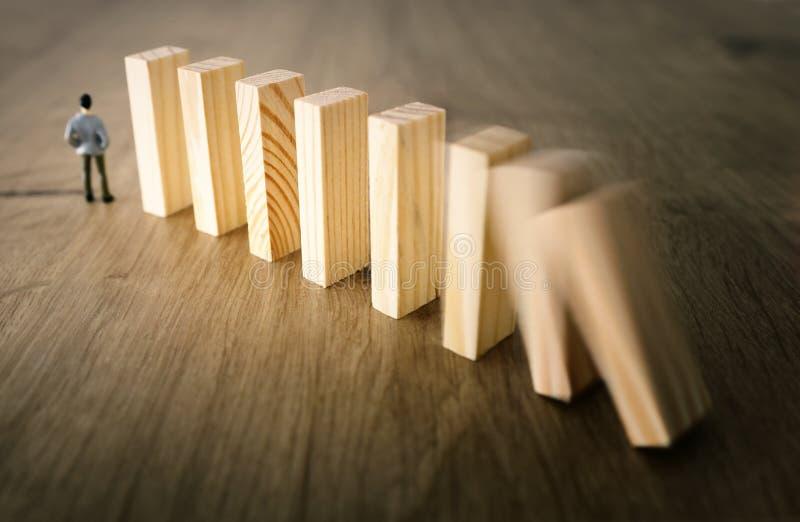 Zaken Een mens bevindt zich voor domino's en schikt hen maar is onbewust van het gevaar van hun daling risicocontrole en stock foto