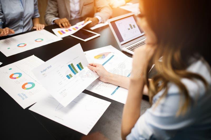 Zaken en bureauconcept - sluit omhoog van commercieel team met praatjes en grafieken in bureau royalty-vrije stock foto's