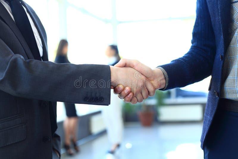 Zaken en bureauconcept - twee zakenlieden die handen schudden royalty-vrije stock foto's