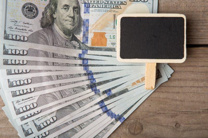 Zaken en financieel concept - honderd dollarsrekeningen en weinig leeg bord stock fotografie