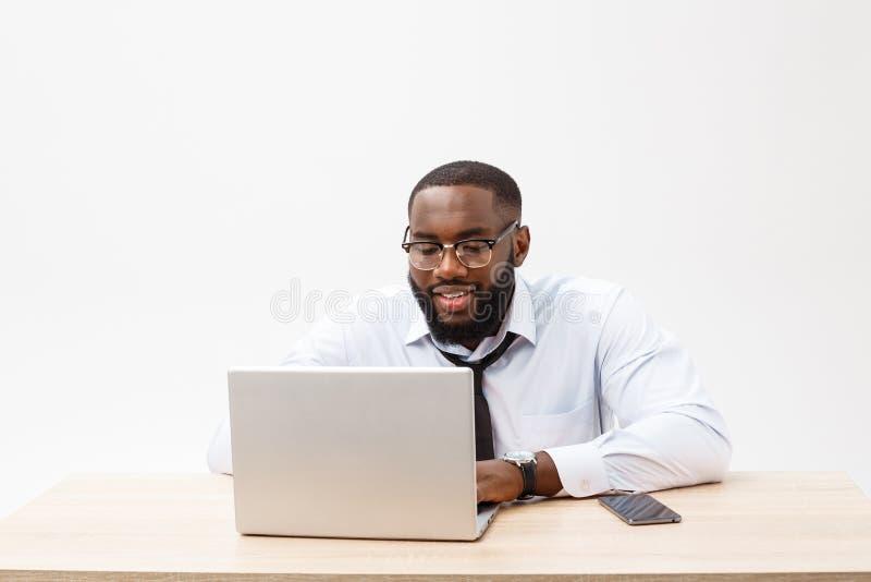 Zaken en succes Knappe succesvolle Afrikaanse Amerikaanse mens die formeel kostuum dragen, die laptop computer voor ver met behul stock foto's