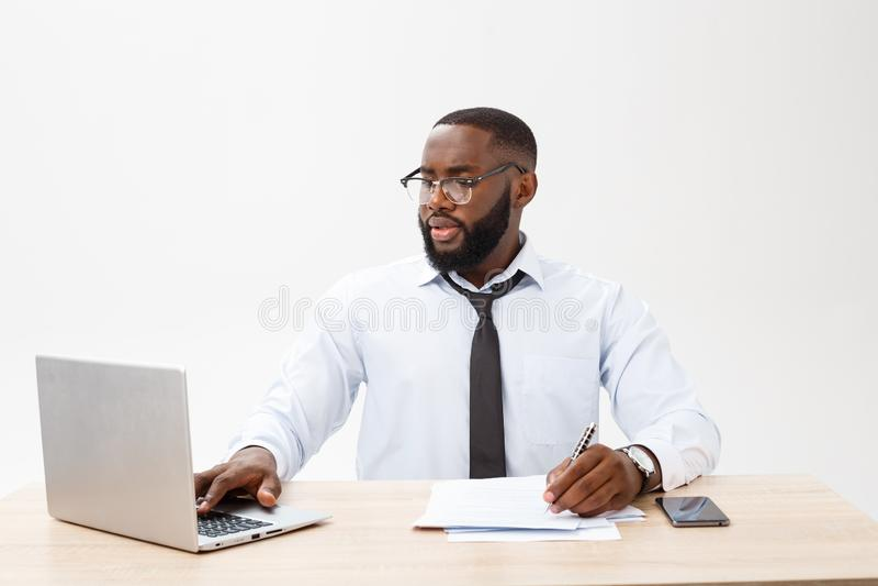 Zaken en succes Knappe succesvolle Afrikaanse Amerikaanse mens die formeel kostuum dragen, die laptop computer voor ver met behul royalty-vrije stock fotografie