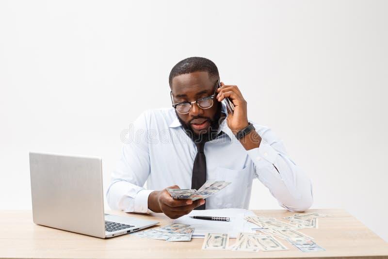 Zaken en succes Knappe succesvolle Afrikaanse Amerikaanse mens die formeel kostuum dragen, die laptop computer voor ver met behul stock fotografie