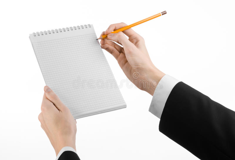 Zaken en verslaggeversonderwerp: de hand van een journalist in een zwart kostuum die een notitieboekje met een potlood op een wit royalty-vrije stock fotografie