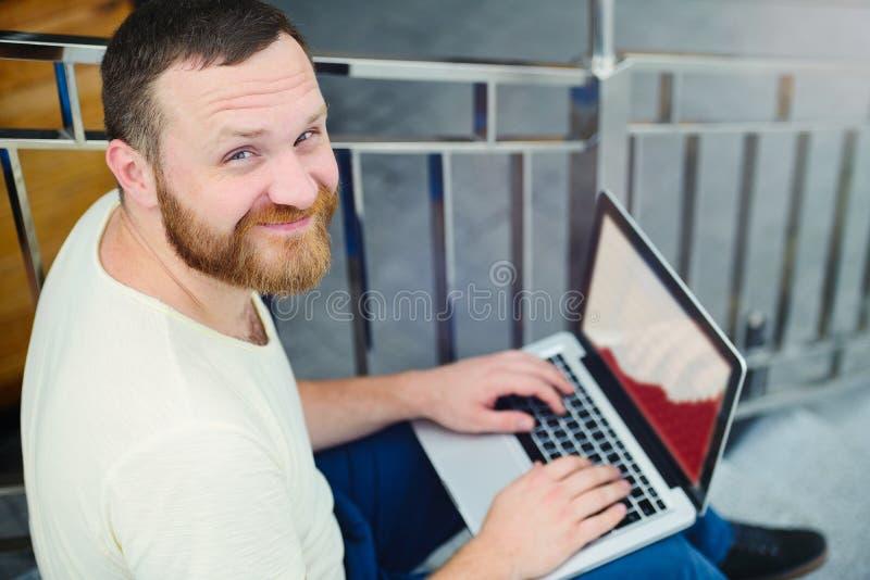 Zaken en vrijheid De gelukkige moderne zakenman, een mens met een baard achter laptop in de stad zit op de stappen en de werkzaam stock afbeeldingen