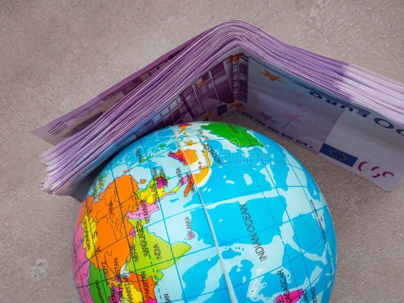 zaken en wereldeconomie Wereldbol en euro internationale geldbankbiljetten Financieel investeringsconcept royalty-vrije stock afbeeldingen