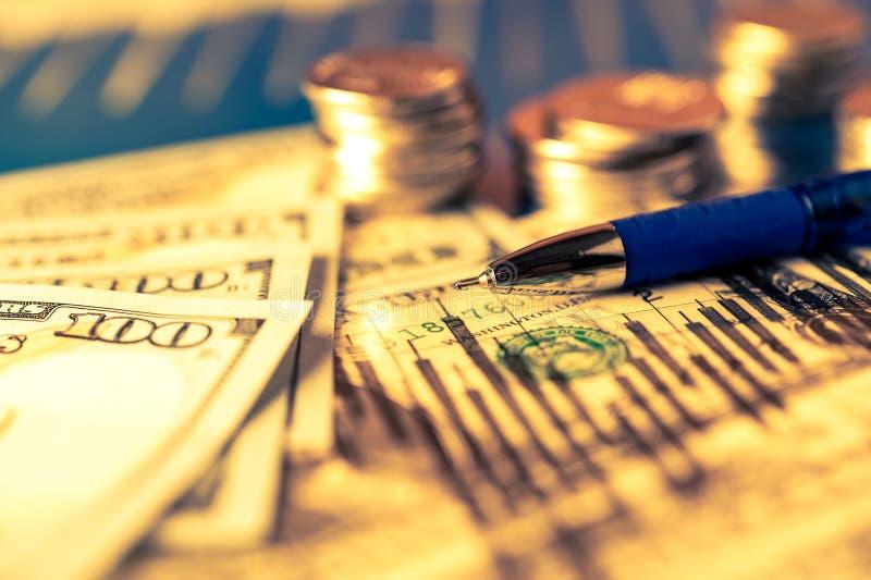 Zaken, financiële achtergrond met dollars, gegevens, pen en stapels muntstukken Boekhoudingsachtergrond stock foto's
