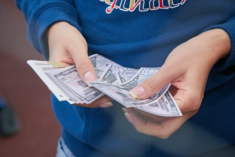 Zaken, financiën, besparing, bankwezen en mensenconcept - sluit omhoog van vrouwenhanden die ons tellen dollar en roebelsgeld stock foto's