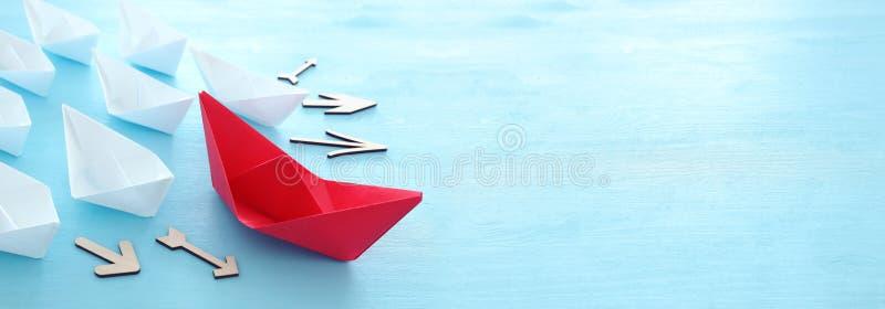 Zaken Het beeld van het leidingsconcept met document boten op blauwe houten achtergrond Één leider die othes leiden royalty-vrije stock afbeeldingen