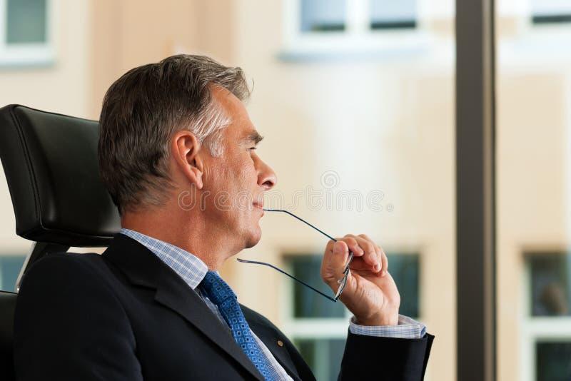 Zaken - het Chef- overwegen in zijn bureau stock afbeelding