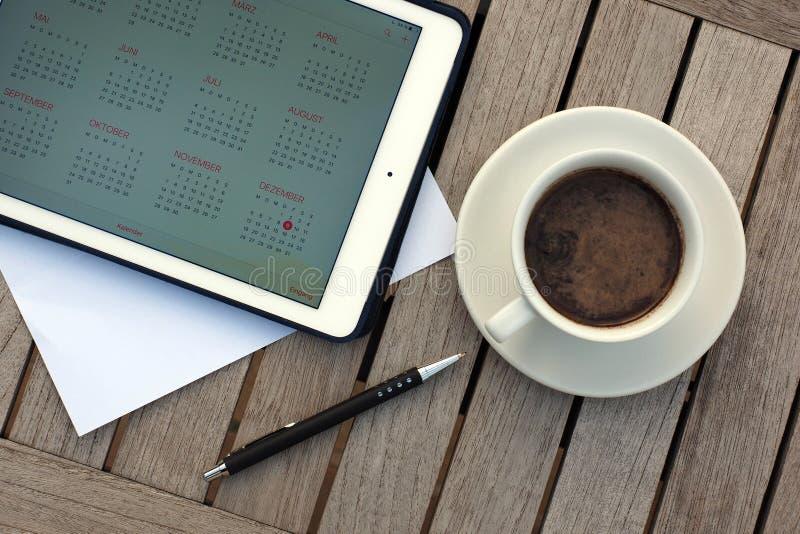 Zaken, kalenders, benoeming Bureaulijst met blocnote, computer, koffiekop stock foto