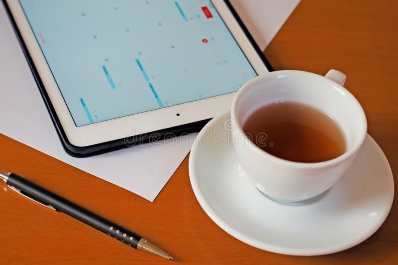 Zaken, kalenders, benoeming Bureaulijst met blocnote, computer, koffiekop stock foto's