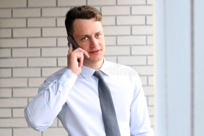 Zaken, mensen en bureauconcept - gelukkige jonge zakenman die smartphone over bureau dichtbij met venster uitnodigen royalty-vrije stock afbeelding