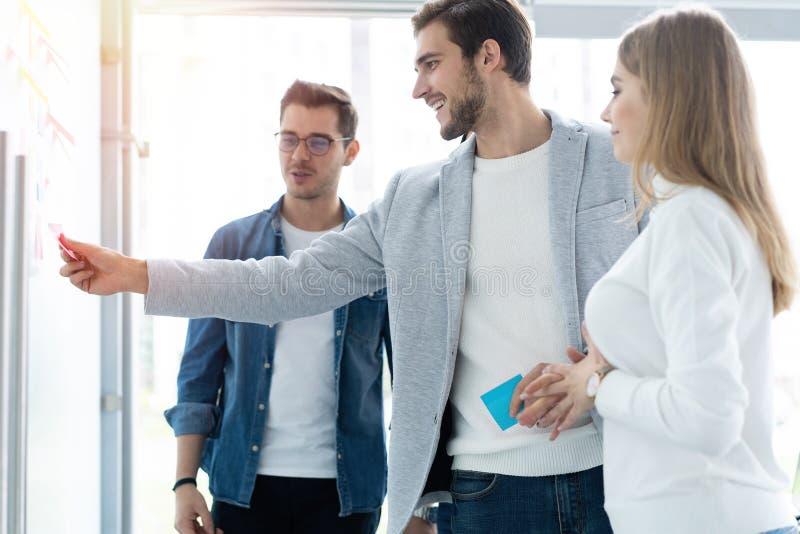 Zaken, onderwijs en bureauconcept - commercieel team met tikraad die in bureau iets bespreken stock afbeeldingen