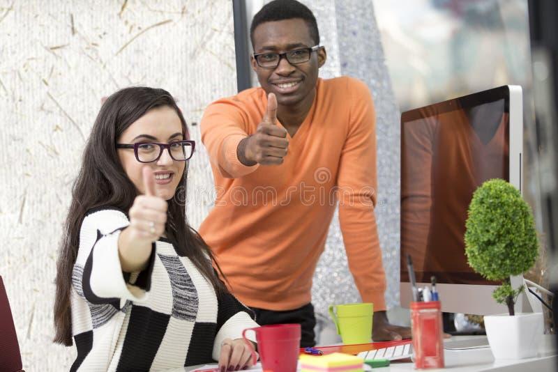 Zaken, opstarten en bureauconcept - gelukkig creatief team die duimen in bureau tonen royalty-vrije stock afbeelding