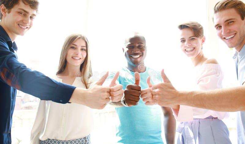 Zaken, opstarten en bureauconcept - gelukkig creatief team die duimen in bureau tonen royalty-vrije stock afbeeldingen