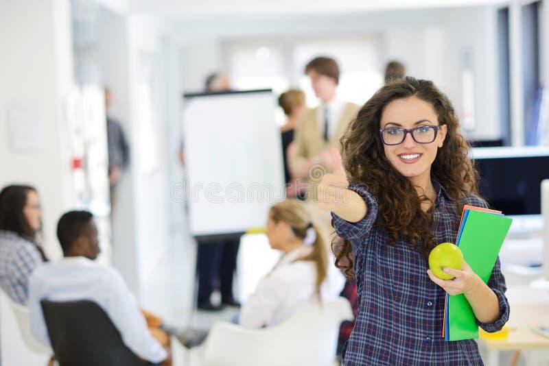Zaken, opstarten en mensenconcept - gelukkig creatief team met computer en omslag in bureau stock afbeelding