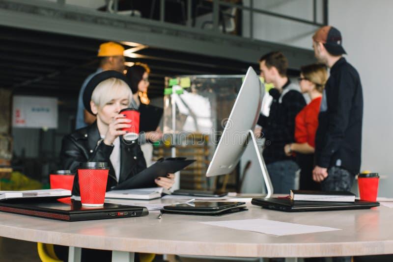 Zaken, opstarten, planning, beheer en mensenconcept - jong meisje in hoed het drinken koffie en het werken bij de lijst stock foto