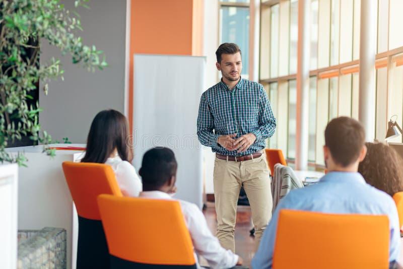 Zaken, opstarten, presentatie, strategie en mensenconcept - mens die tot presentatie maken aan creatief team op kantoor royalty-vrije stock afbeeldingen