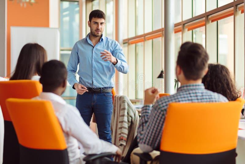 Zaken, opstarten, presentatie, strategie en mensenconcept - mens die tot presentatie maken aan creatief team op kantoor stock afbeeldingen