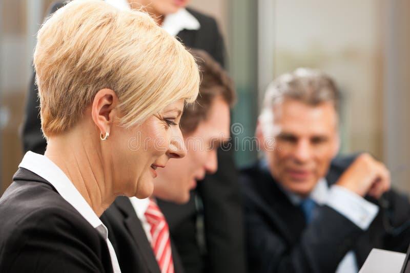 Zaken - teamvergadering in een bureau stock afbeelding