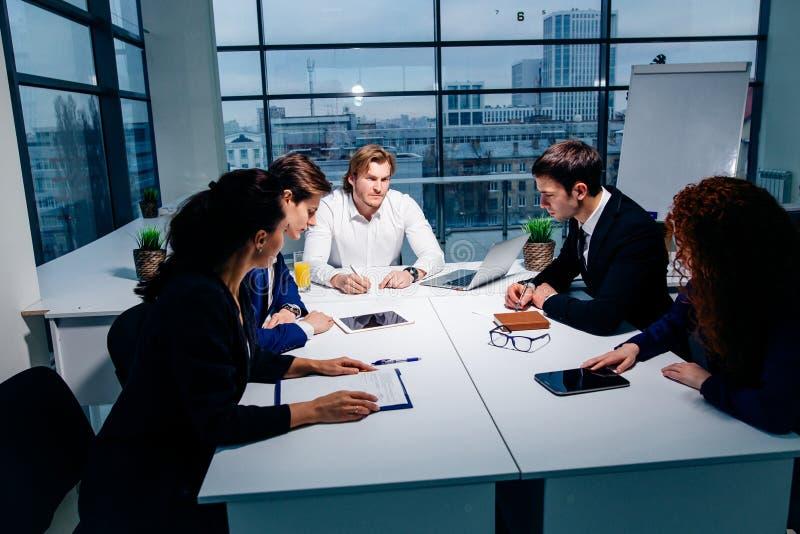 Zaken, technologie en bureauconcept - glimlachende werkgever die aan commercieel team spreken royalty-vrije stock foto