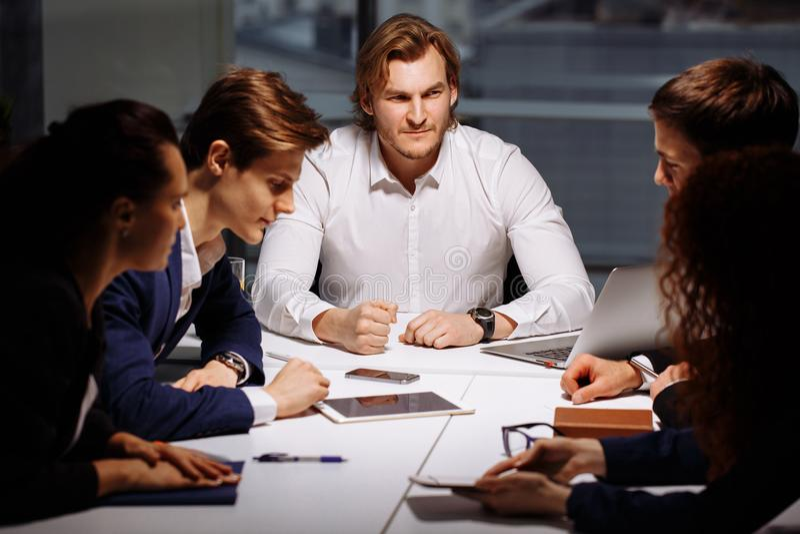 Zaken, technologie en bureauconcept - glimlachende werkgever die aan commercieel team spreken stock foto