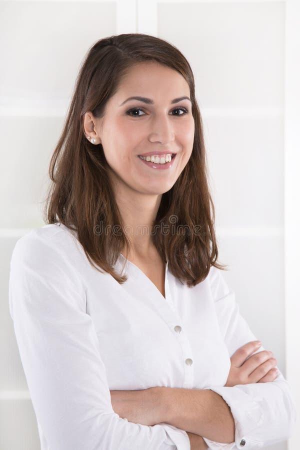 Zaken: tevreden vrij donkerbruine vrouw met gevouwen wapens in een wh stock foto