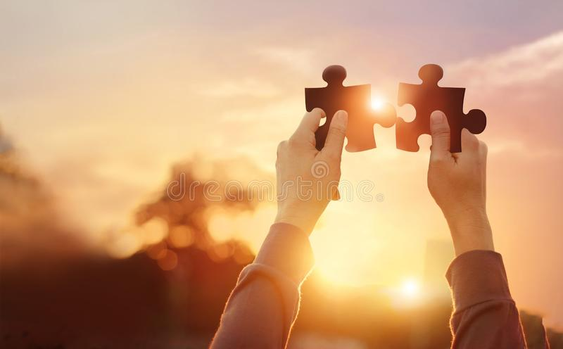 Zaken van groepswerk, symbool van succes, puzzel het in hand verbinden, bedrijfs planning en strategie op zonsondergang royalty-vrije stock afbeelding