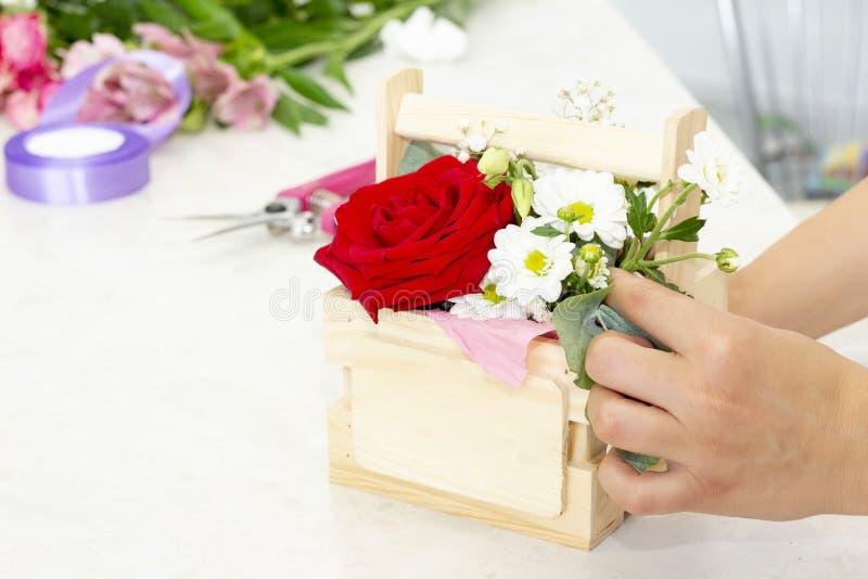 Zaken, verkoop en floristry concept - sluit omhoog van de holdingsbos van de bloemistvrouw bij bloemwinkel Zachte schaduwen van v royalty-vrije stock afbeelding