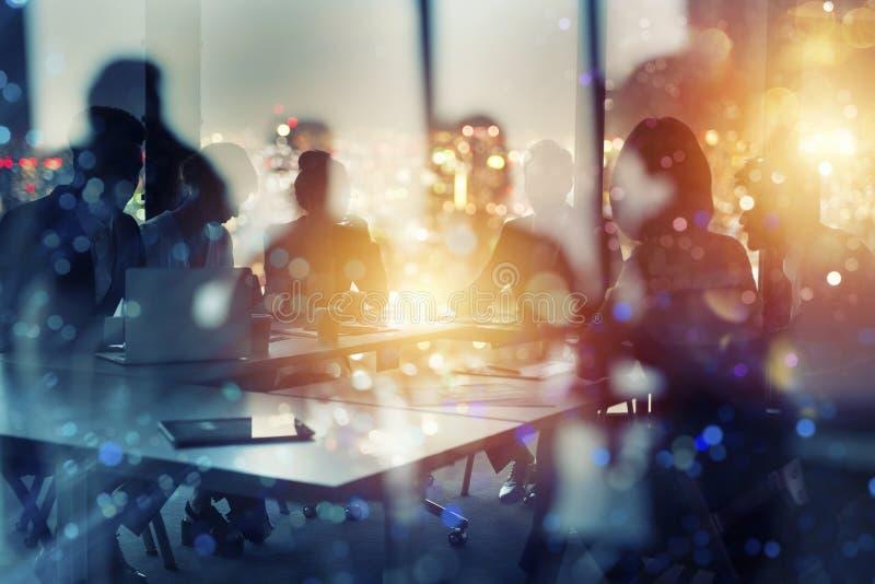 Zakenlieden die in bureau bij nacht samenwerken Concept groepswerk en vennootschap Dubbele blootstelling royalty-vrije stock afbeeldingen