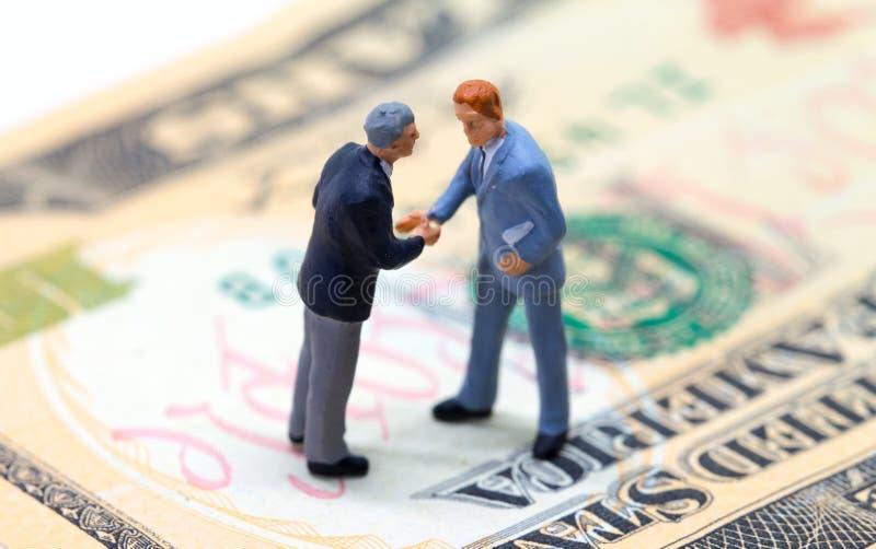 Zakenlieden die handen op Amerikaanse dollar schudden Uiterst kleine zakenliedenbeeldjes op geldachtergrond royalty-vrije stock fotografie