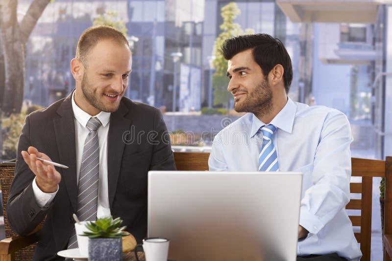 Zakenlieden die ideeën op laptop computer bespreken royalty-vrije stock fotografie