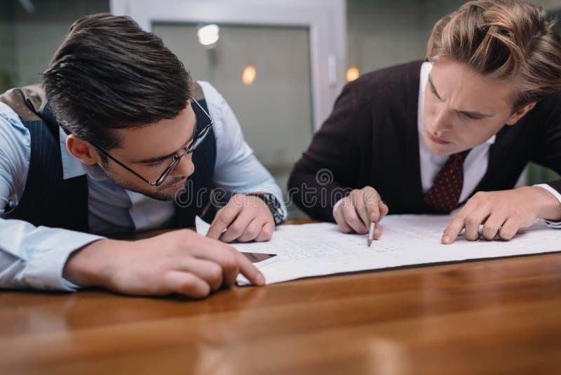 zakenlieden die samen met blauwdruk werken stock afbeelding