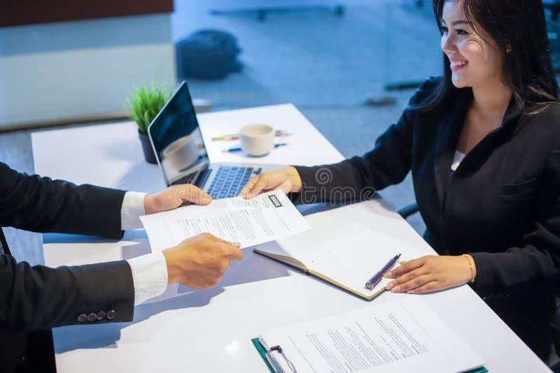 Zakenlieden en Onderneemsters die documenten voor baan bespreken inter stock afbeelding