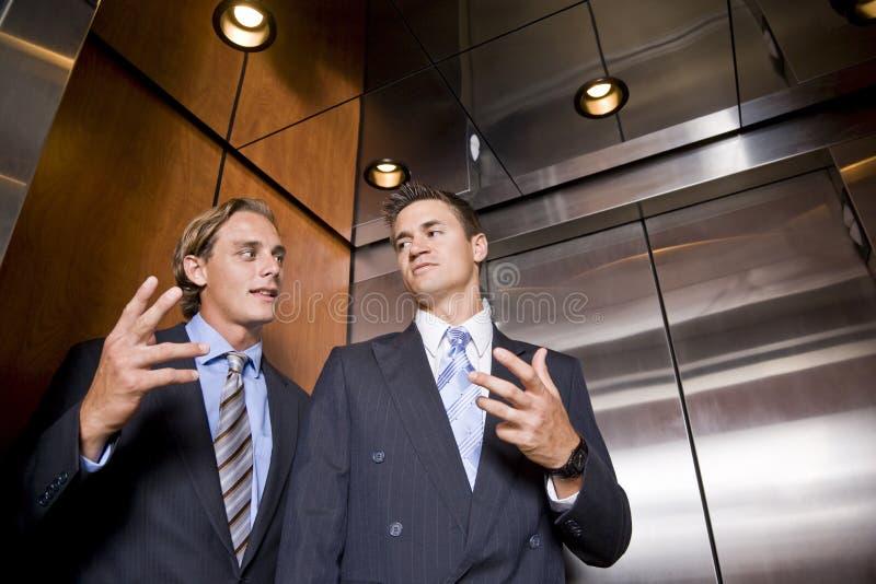 Zakenlieden in lift het converseren royalty-vrije stock foto's
