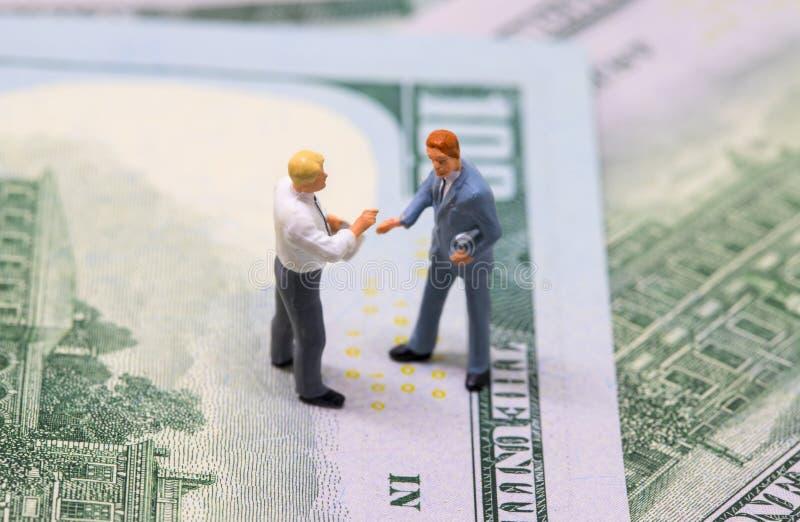 Zakenliedenbeeldjes die handen op contant geld schudden Uiterst kleine zakenliedenmodellen op geldachtergrond royalty-vrije stock afbeeldingen