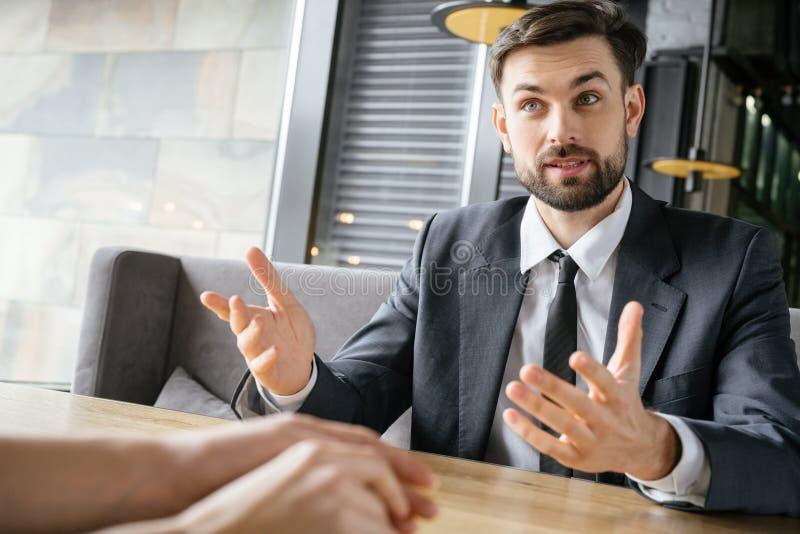 Zakenlui die bedrijfslunch hebben bij de mens die van de restaurantzitting over het werkclose-up spreken royalty-vrije stock foto's