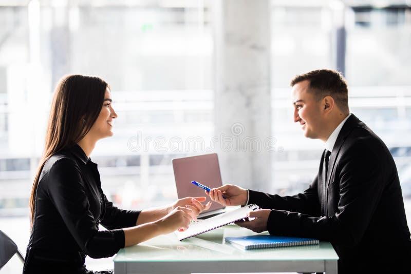 Zakenlui die bij een lijst zitten en een contract ondertekenen op kantoor royalty-vrije stock foto