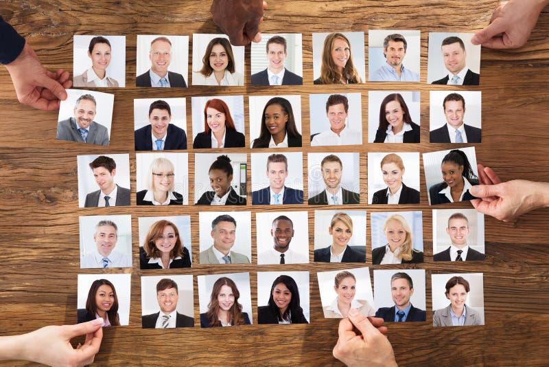 Zakenlui die de Kandidaatportretfoto selecteren stock foto's