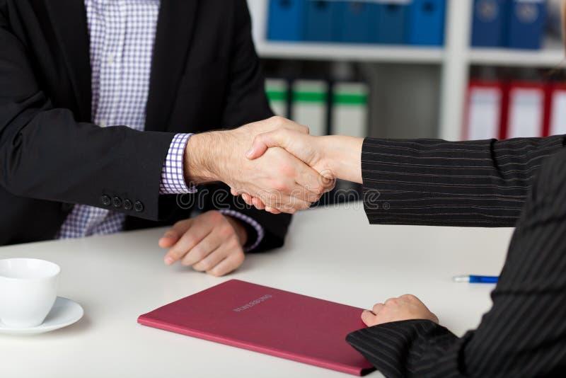 Zakenlui die Handen schudden bij Bureau stock afbeelding