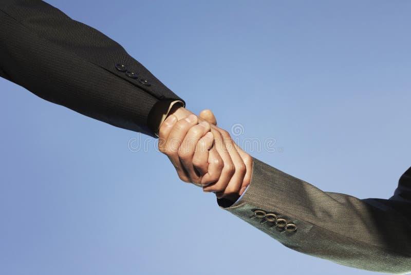 Zakenlui die handen schudden tegen duidelijke hemel royalty-vrije stock foto