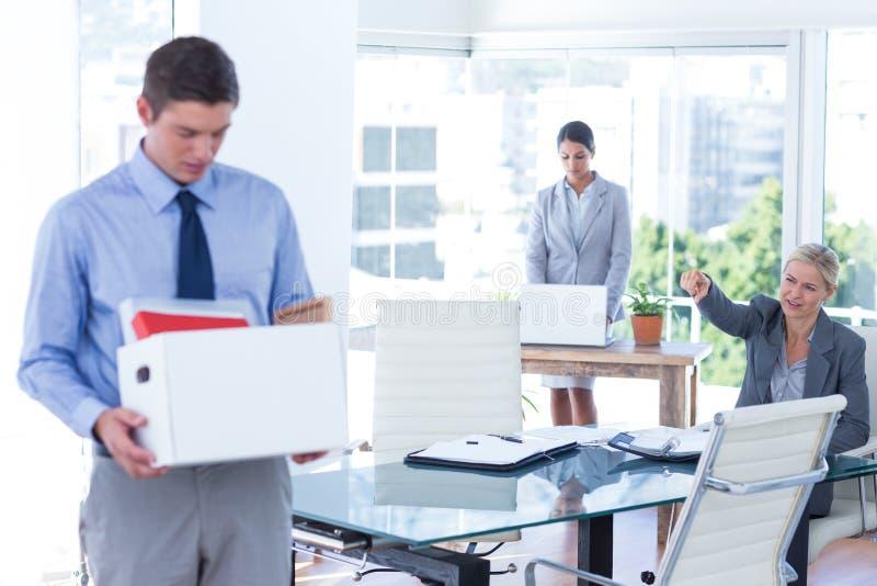Zakenlui die hun bezittingen in doos dragen stock fotografie