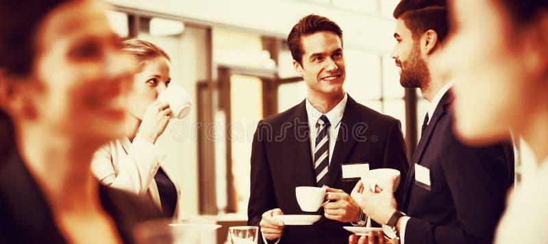 Zakenlui die met elkaar interactie aangaan terwijl het hebben van koffie royalty-vrije stock foto's