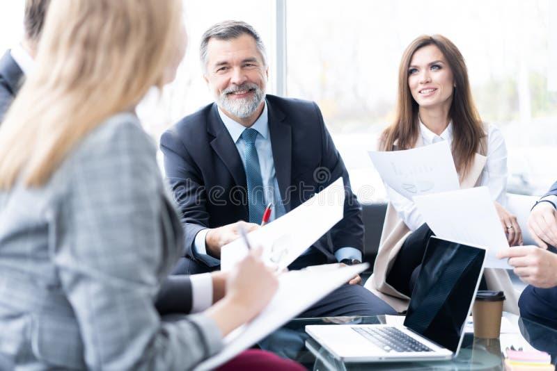 Zakenlui die samen in conferentieruimte tijdens vergadering op kantoor bespreken royalty-vrije stock afbeeldingen