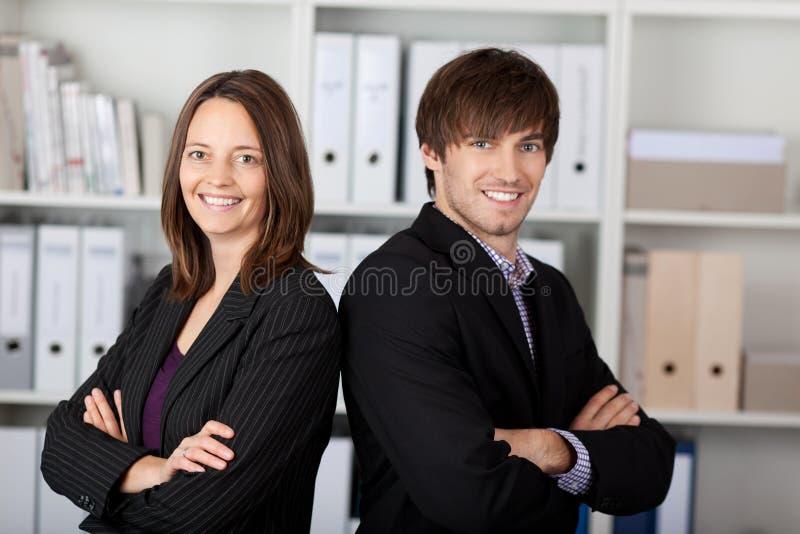 Zakenlui met Gekruiste Wapens Status in Bureau stock afbeeldingen