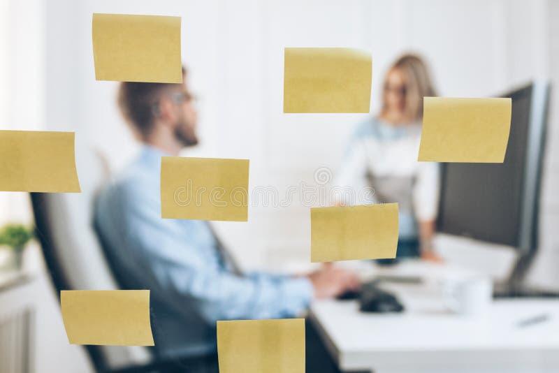 Zakenlui op het kantoor achter een glasmuur stock afbeelding