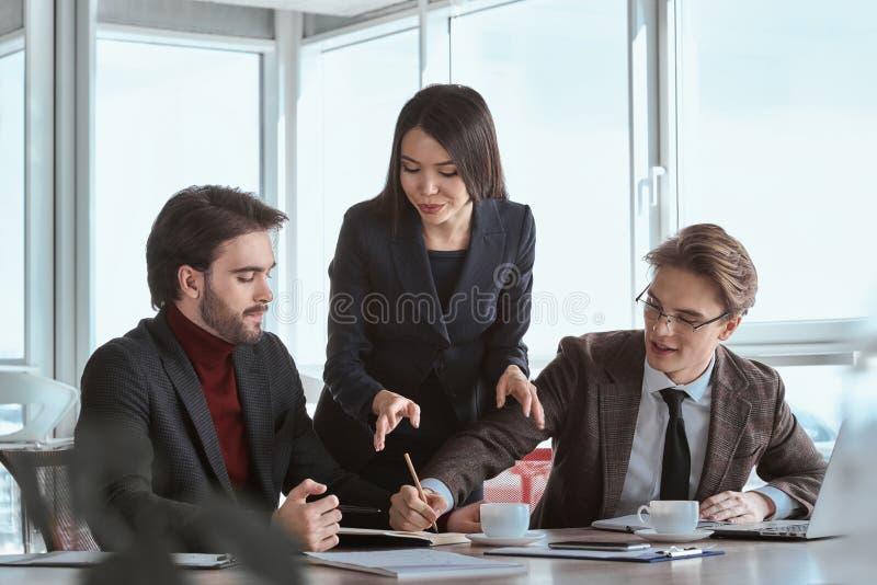 Zakenlui op kantoor die samen het zitten contra ondertekenen werken stock foto